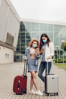 Duas mulheres com máscaras protetoras estão paradas perto do aeroporto e procuram um local em um telefone celular
