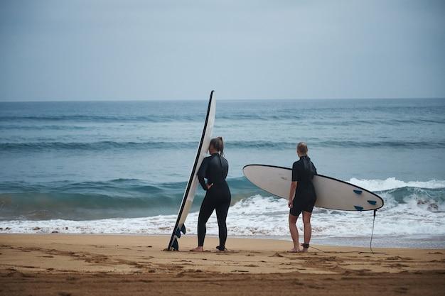 Duas mulheres com roupas de neoprene e pranchas de surfe se preparando para entrar na água em um dia frio de verão