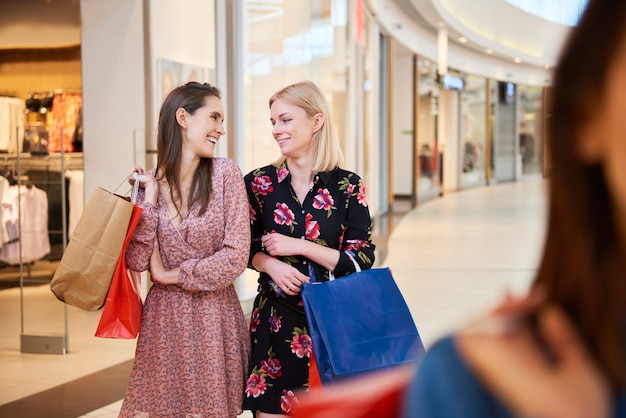 Duas mulheres com sacolas de compras no shopping