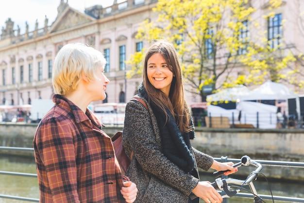 Duas mulheres com uma bicicleta andando em berlim