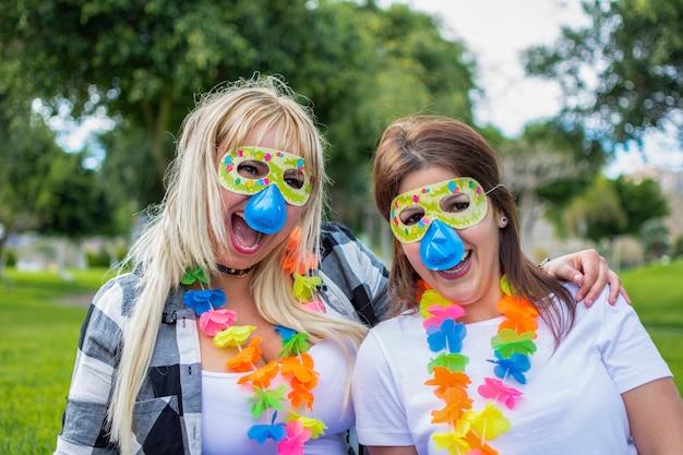 Duas mulheres com uma máscara, um nariz de palhaço e um colar de aniversário, comemorando a festa no parque.