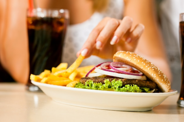 Duas mulheres comendo hambúrguer e bebendo refrigerante