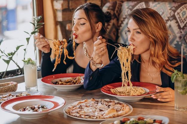 Duas mulheres comendo macarrão em um restaurante italiano