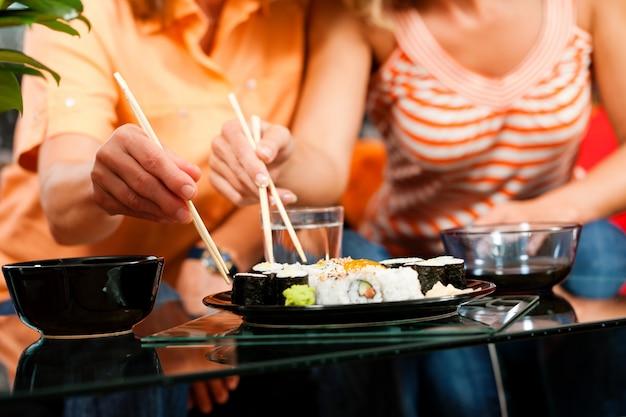 Duas mulheres, comer sushi