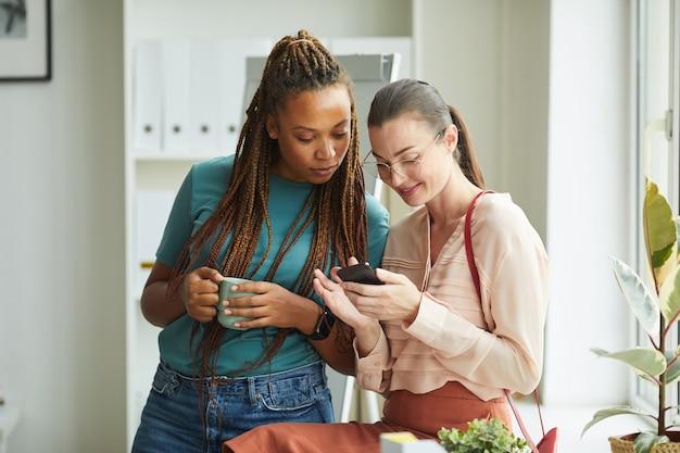 Duas mulheres contemporâneas olhando para a tela do smartphone enquanto estão no escritório