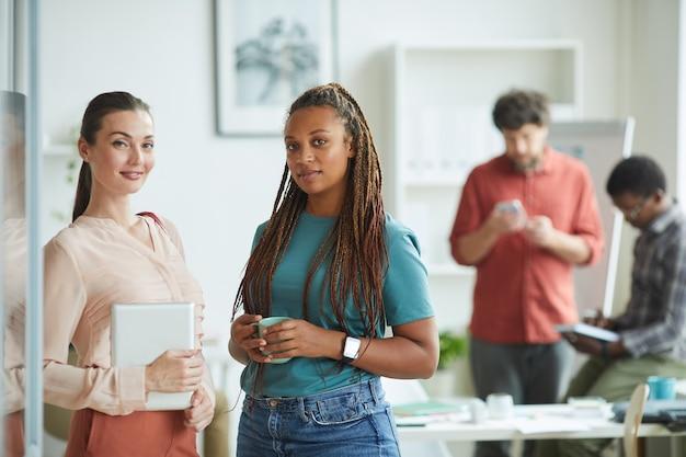 Duas mulheres contemporâneas posando com confiança em pé no escritório