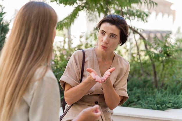 Duas mulheres conversando ao ar livre usando linguagem de sinais