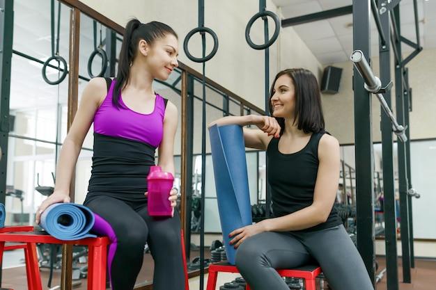 Duas mulheres conversando com colchonetes no ginásio