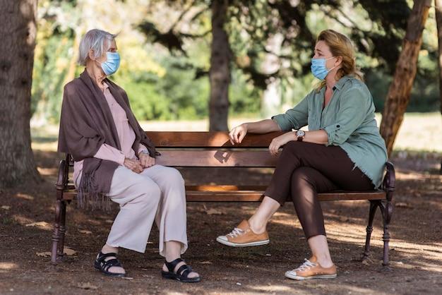 Duas mulheres conversando com máscaras médicas ao ar livre em uma casa de repouso