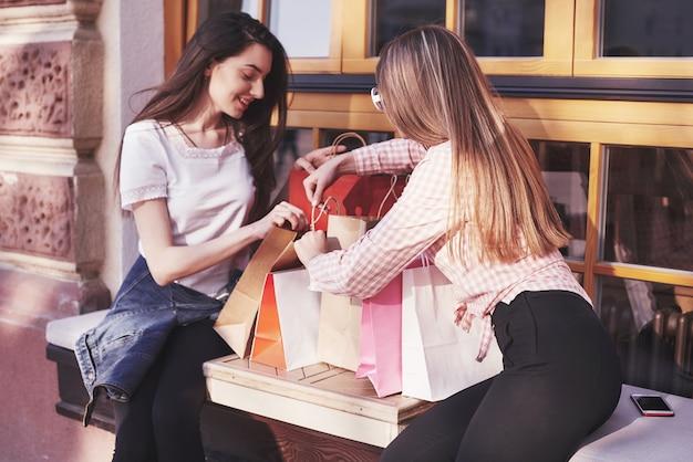 Duas mulheres conversando depois de fazer compras na rua perto da janela.