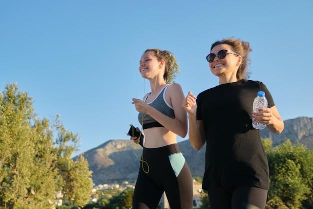 Duas mulheres correndo. adolescente de mãe e filha correndo ao ar livre na estrada nas montanhas num dia ensolarado de verão. família, estilo de vida saudável e ativo.