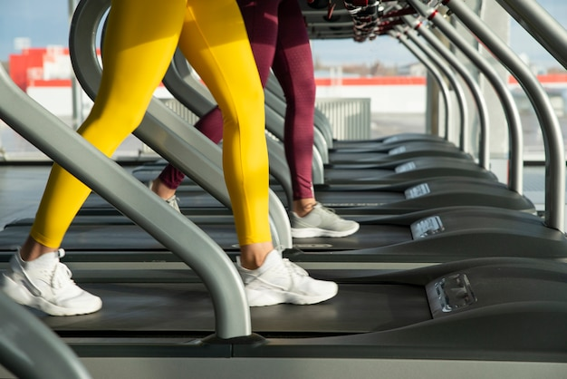 Duas mulheres correndo na esteira na academia