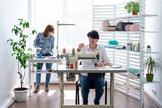 Duas mulheres costuram acessórios de bolsa em uma máquina de costura e se comunicam