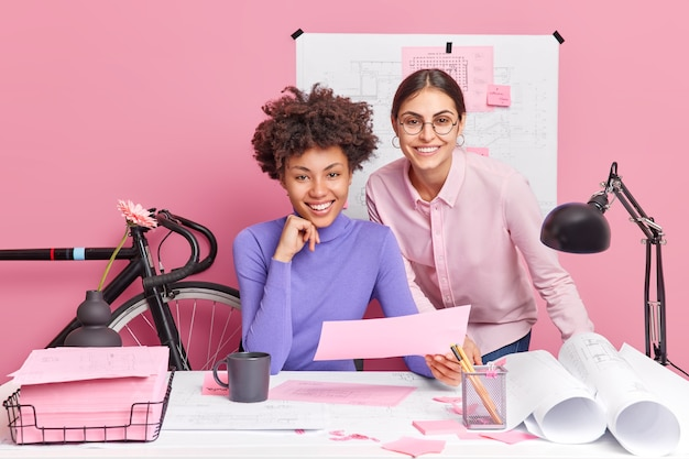Duas mulheres criativas e diversificadas colaboram juntas para fazer os blueprints trabalharem em uma pose de novo projeto em um espaço de coworking para desfrutar de sua ocupação