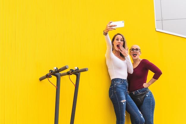 Duas mulheres de amigo tomando selfie sobre uma parede amarela ao ar livre.