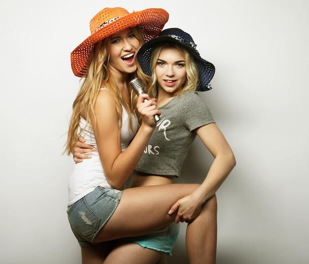 Duas mulheres de beleza com um microfone