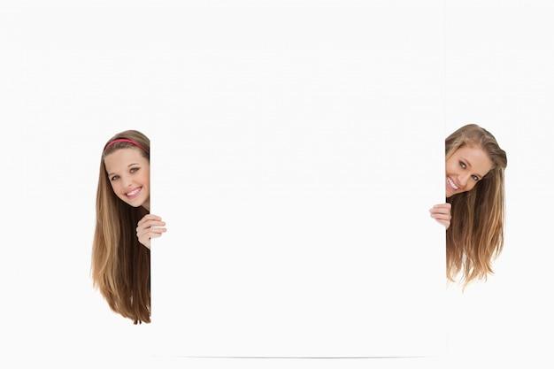 Duas mulheres de cabelo comprido atrás de um sinal em branco