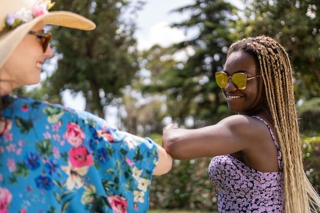 Duas mulheres de diferentes etnias com roupas de verão, acotovelando-se em um jardim.