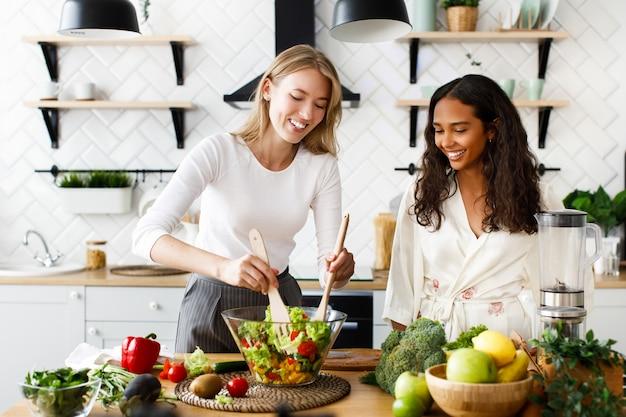 Duas mulheres de diferentes nacionalidades estão sorrindo e cozinhando uma salada na cozinha