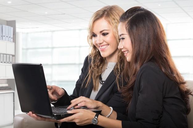 Duas mulheres de negócios amigáveis sentado e discutindo novas idéias usando o computador portátil