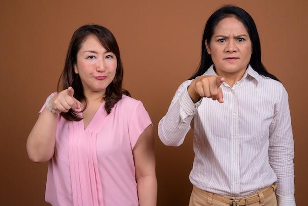 Duas mulheres de negócios asiáticas maduras juntas contra a parede marrom