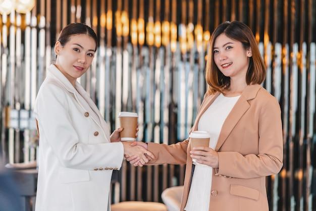 Duas mulheres de negócios asiáticas segurando o copo de papel de café e a mão tremendo quando o sucesso do parceiro de negócios acordo juntos na sala de reuniões