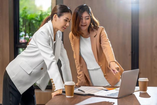 Duas mulheres de negócios asiáticas trabalhando com o parceiro comercial via laptop de tecnologia na moderna sala de reuniões