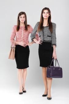 Duas mulheres de negócios bem-sucedidas de terno. gêmeos com bolsas da moda