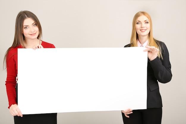 Duas mulheres de negócios com formulário em branco sobre fundo cinza