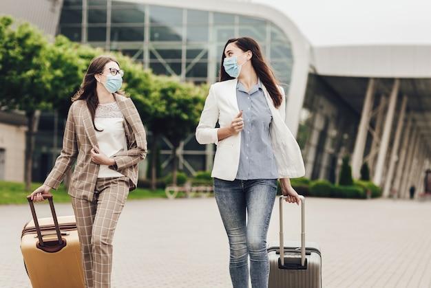 Duas mulheres de negócios com máscaras protetoras e malas perto do aeroporto