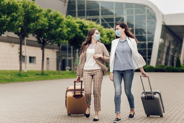 Duas mulheres de negócios com máscaras protetoras e malas vão para o aeroporto