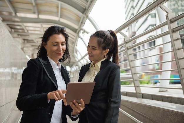 Duas mulheres de negócios com tablet na cidade
