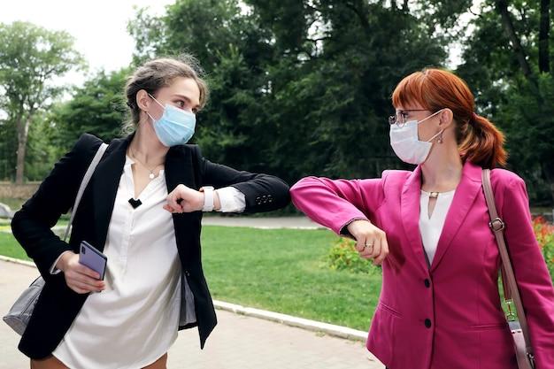 Duas mulheres de negócios cumprimentando os cotovelos