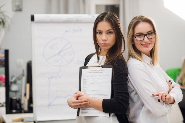 Duas mulheres de negócios, em pé no escritório na frente do flip chart