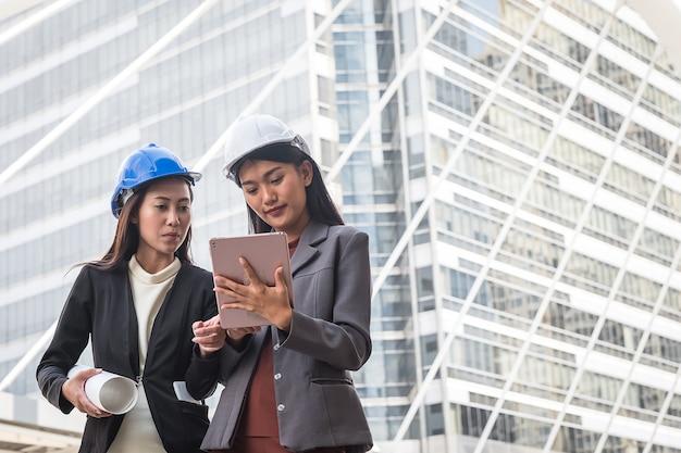 Duas mulheres de negócios, engenheiros industriais em frente a bui