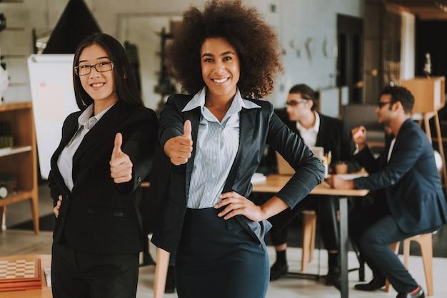 Duas mulheres de negócios estão mostrando os polegares para cima e sorrindo.