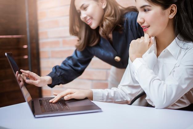 Duas mulheres de negócios jovens são informações de análise na tela do laptop, reunião de negócios