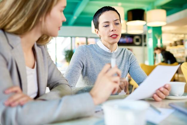 Duas mulheres de negócios lendo documentos no café