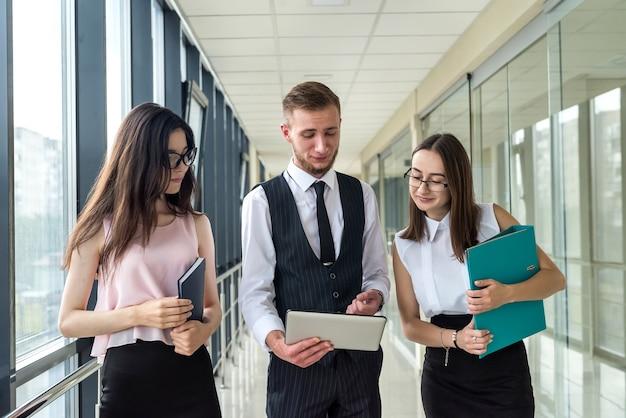 Duas mulheres de negócios sérias e um homem mostram o documento e falam sobre o erro ao subordinado no corredor do escritório. conceito de reunião