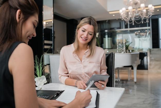Duas mulheres de negócios tendo reunião no lobby do hotel.
