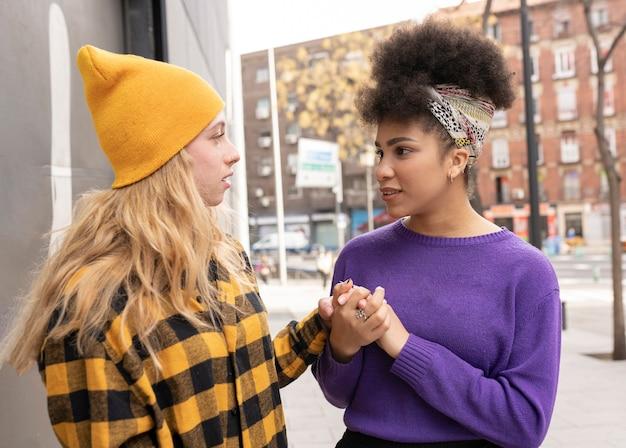 Duas mulheres de raças diferentes, de mãos dadas, rua abaixo