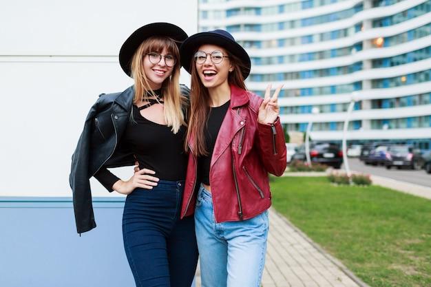 Duas mulheres de sorriso despreocupadas posando na cidade moderna. vestindo jeans e jaqueta de couro de chapéu de lã.