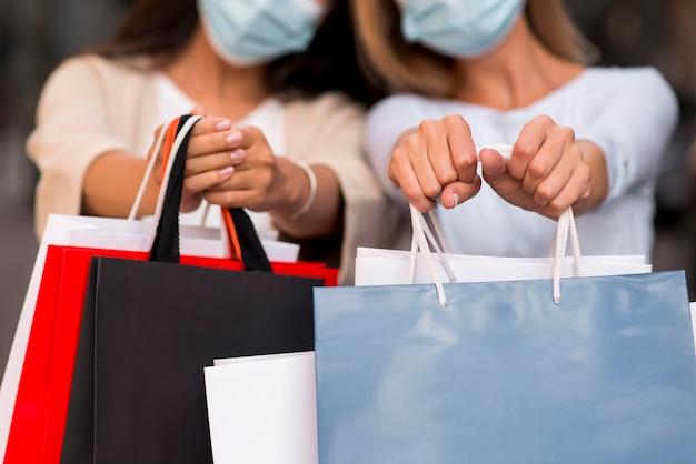 Duas mulheres desfocadas com máscaras médicas segurando sacolas de compras com itens à venda