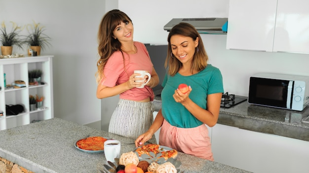 Duas mulheres desfrutando de pizza na cozinha em apartamento moderno.