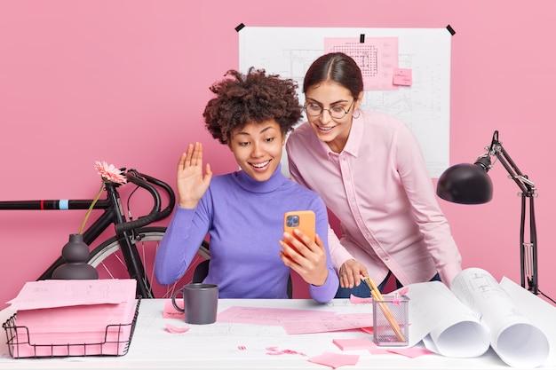 Duas mulheres diferentes discutem ideias para um projeto comum futuro fazem videochamada com um parceiro internacional online, criam esboços, posam em um espaço de coworking contra uma parede rosa, tendo um cérebro