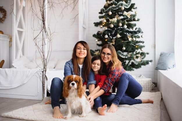 Duas mulheres e uma menina com um cachorro se abraçando perto da árvore de natal