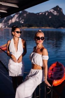 Duas mulheres elegantes com roupas brancas de verão e óculos escuros perto do mar