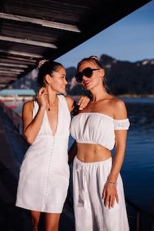 Duas mulheres elegantes com roupas brancas de verão perto do mar ao entardecer