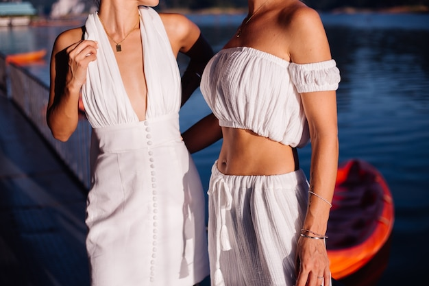 Duas mulheres elegantes com roupas de verão brancas posando perto da água
