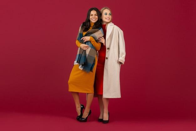 Duas mulheres elegantes com vestido e casaco da moda outono inverno posando isoladas na parede vermelha